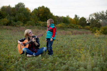 A boy and his mother are playing and singing guitar in the autumn forest