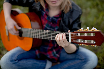 a girl sits on the grass with a guitar playing