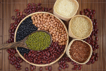 Cereal grains and Seeds beans(Black Bean, Red Bean, Peanut, Mung Bean, Thai Jasmine Rice, Brown Rice and White Rice) useful for health in wood spoons on wood background.