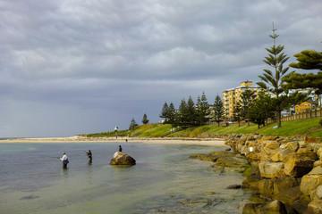 Fishermen standing in water at seaside