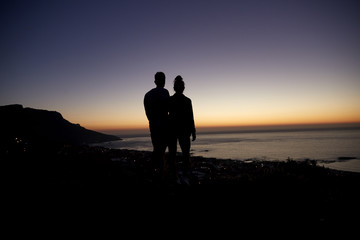 Couple strolling by the sea at sunset on a beach, silhouette