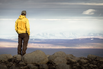 Man standing on mountain, looking relaxed towards snowy mountain range.