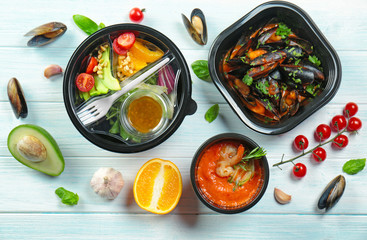 Plastic containers with delicious food on wooden table