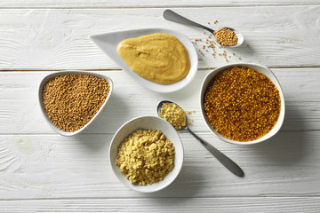 Mustard seeds, powder and sauces in dishes on wooden table