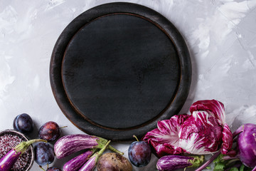 Assortment raw organic of purple vegetables mini eggplants, onion, beetroot, radicchio salad, plums, kohlrabi, flower salt, empty chopping board over gray concrete background. Top view with space.
