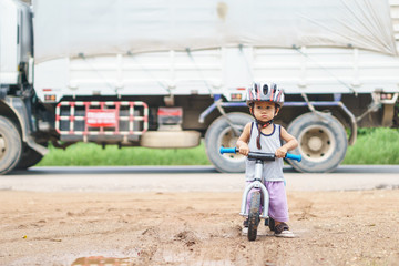 Asian boy about 1 year and 6 months is playing with baby balance bike near rural street while car passing by