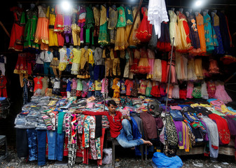 A costume vendor checks his mobile phone as he waits for customers in Rishikesh