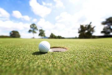 Golf ball near hole, background blue sky