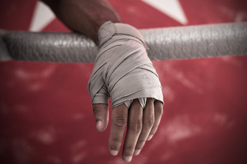 Close up of hand of boxer leaning on ropes on a boxing ring.