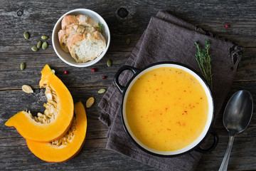 Pumpkin cream soup in bowl on rustic wooden table. Top view, copy space for text