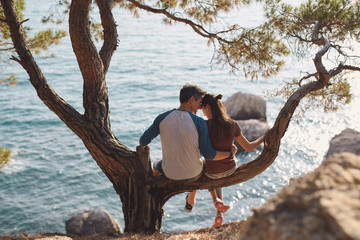 romantic young couple in love together. Happy young couple in love sitting and kissing on a tree branch on sea in background