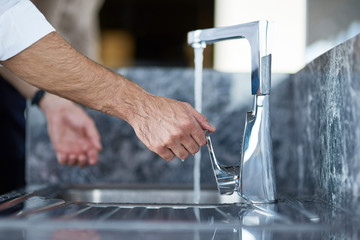 Close up of a pleasant man washing his hands