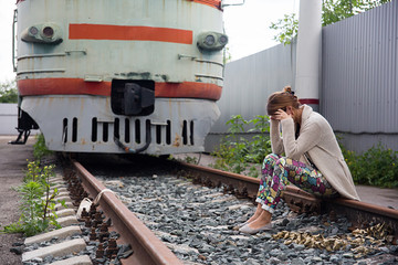 The girl is sitting on the rails at the train. Suicide