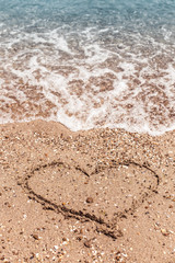 Drawing of a heart on the sand on the beach and wave with foam. Sea travel and holiday. Selective focus