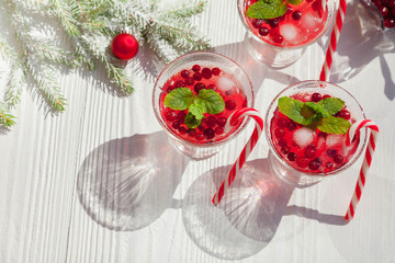 Cranberry drinks with lollipop candy cane on white rustic wooden table, Christmas background