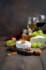 Variety of cheese with grapes, walnuts and wine, selective focus, copy space, vertical