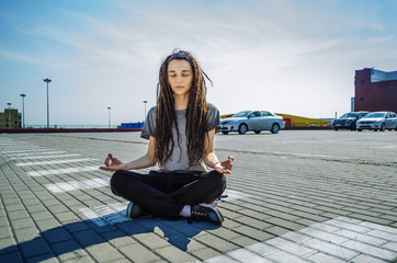 A girl with dreadlocks in a lotus pose in the city in a car park. Yoga and meditation in the street