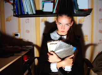 anger schoolgirl in school suit holding books in the room