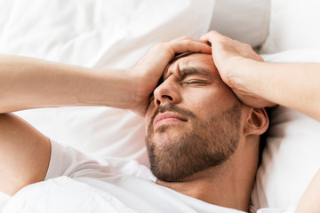 close up of man in bed suffering from headache