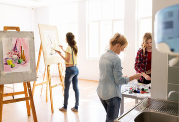 woman artists with colors painting at art school