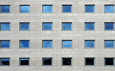 Gray stone modern facade of a building with windows reflecting the sky