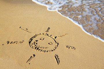 Drawing sun smile in the sand beach background.