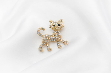 Wall Mural - Brooch golden kitten with diamonds on silk fabric