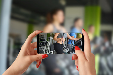 A woman shoots video with phone of group people while they train at a gym