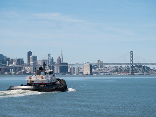 Tugboat on sea against cityscape