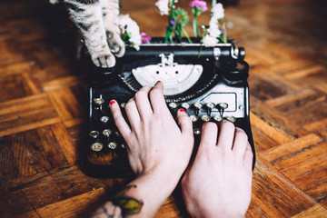woman typing with a vintage typewriter with flowers and cat