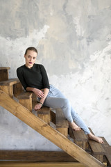 Dark haired woman sitting on wooden stairs while looking at camera