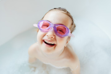 Cute young girl with swim goggles laughing in a bathtub