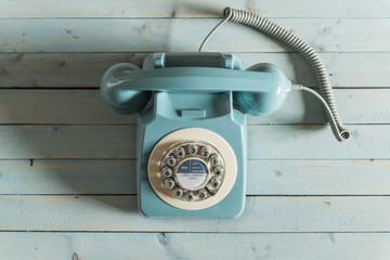 A blue retro telephone on a blue background