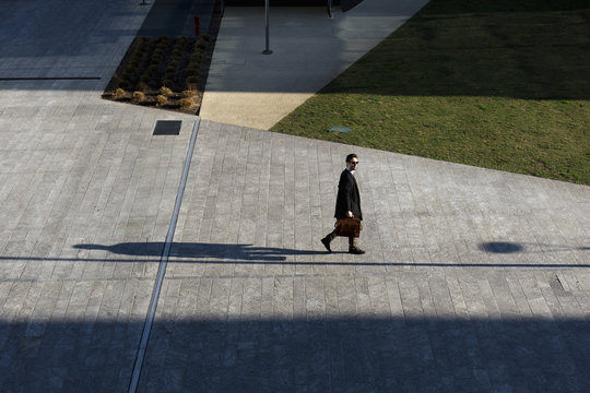 Young man walking with his briefcase out of the office building