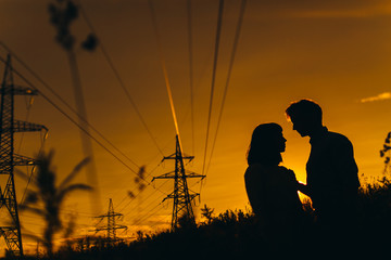 Silhouettes of couple under power lines
