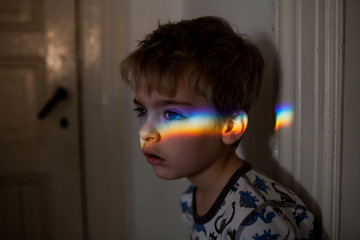 Boy looking forward with rainbow of light across his face.