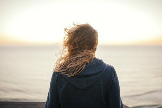 An anonymous blond woman standing in the wind looking at the sea or ocean