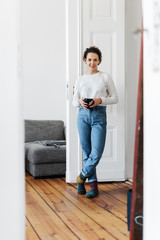 Young woman standing in her apartment.