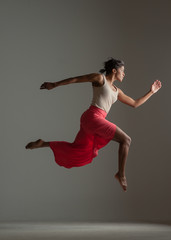 Black woman in red skirt leaping