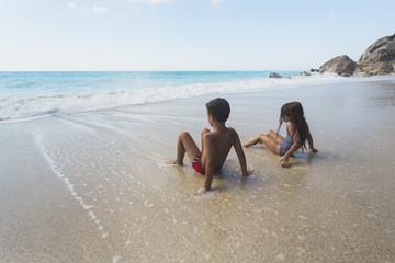 Children sitting on a beach.