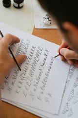 Person write alphabet with straight calligraphy pen