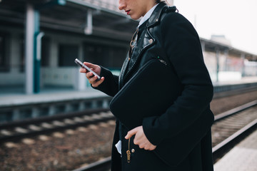 Woman browsing on her mobile phone on train station