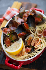 Close-up of spaghetti with vongole shells and mussels in tomato sauce, selective focus, shallow depth of field