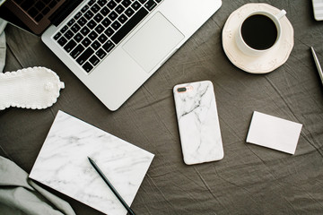 Morning coffee, laptop, marble diary, glasses in bed with grey sheet and pillows. Flat lay, top view home office background.