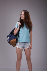Fashion beautiful girl in a blue t-shirt with shorts with backpack on a gray background.