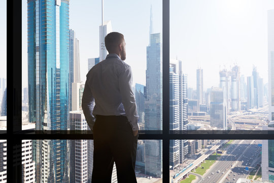 Businessman Looking At Cityscape Through Window