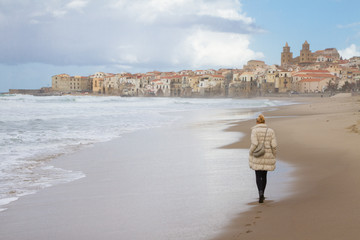 Solitary woman walking empty beach of Cefalu in winter time, Sicily, south Italy.