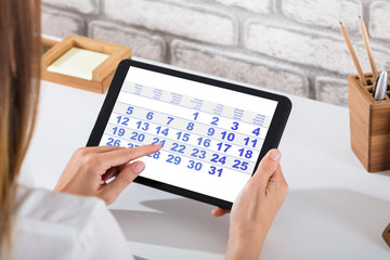 Businessperson Holding Digital Tablet With Calendar On Screen