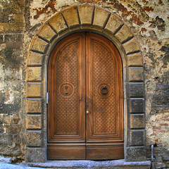 Old brown wooden door in ancient house, Tuscany