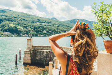 young woman touching her hair in fron of calm water of lake in sunny summer day in italy